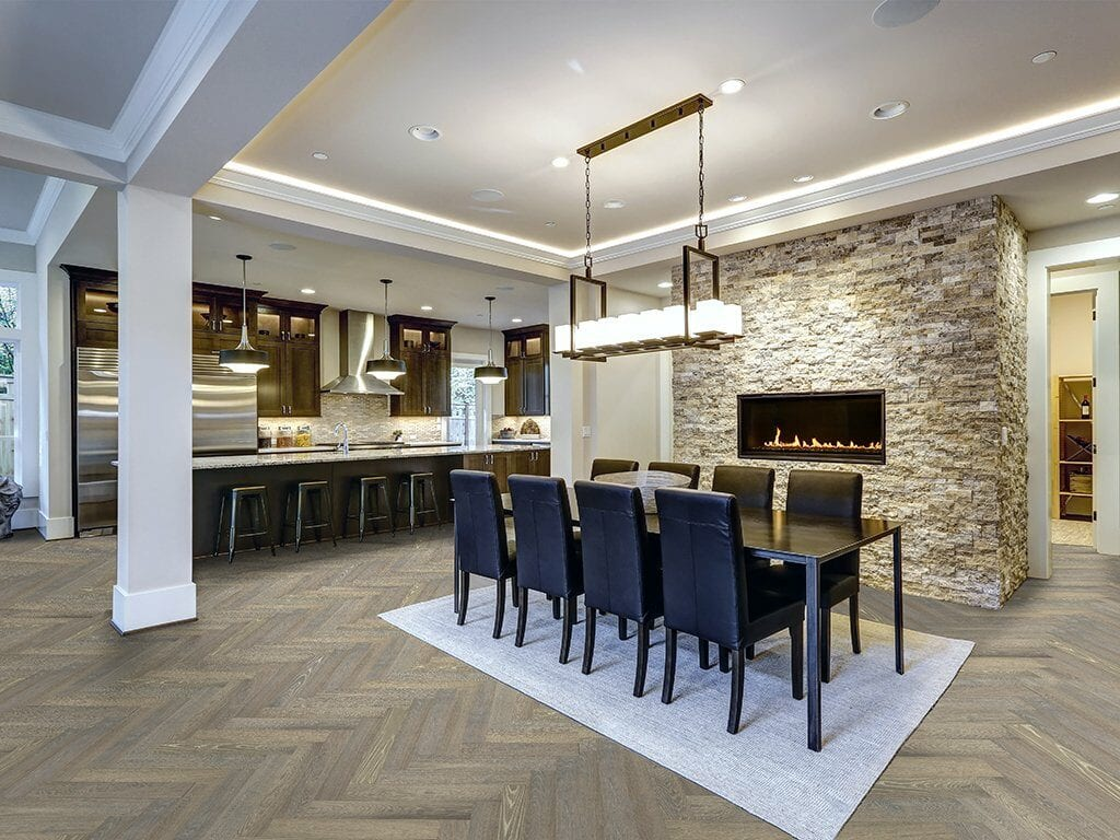 Modern open floor plan dining room design accented with stone fireplace wall facing black dining table lined with leather chairs and illuminated by rectangular chandelier. Northwest, USA